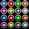 Right arrow white icons in round glossy buttons on black background - Right arrow white icons in round glossy buttons with steel frames on black background. The buttons are in two different styles and eight colors.