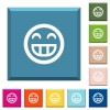Laughing emoticon white icons on edged square buttons in various trendy colors