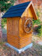 A lonely, wooden draw-well in the garden, with pine forest in the background - Draw-well in the forest-like garden