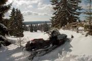 A snowmobile is waiting for a ride in the snow - Snowmobile in the snow