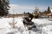 A man is preparing to ride on a snowmobile - Man with a snowmobile