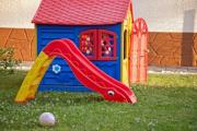 Plastic outdoor slide and toy house in a garden - Slide and toy house