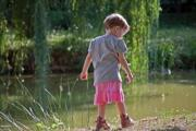 A girl is walking on the bank of a pond - Little girl