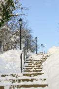 A snowy outdoor stairway with street lamps - Winter stairway