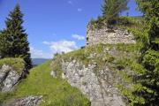 Ruins of an old castle wall on a hill in the mountains - Castle ruin on the hill