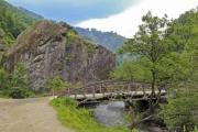 An old, rusty bridge over the mountain river - Bridge over the river
