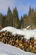 A woodpile with beautiful winter background - Snow-covered woodpile