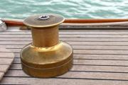 Oldtimer yacht's teak wooden deck with bronze windlass - Windlass