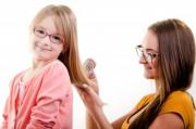 Elder sister is combing little sister's hair - Sisters