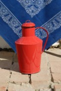 Beautiful red milk vessel in front of a nice blue cloth - Milk vessel
